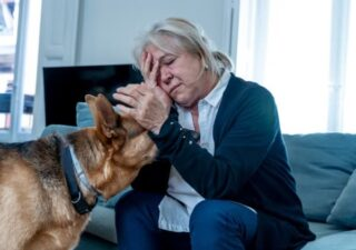 Older woman sitting with one hand on head and the other petting her dog
